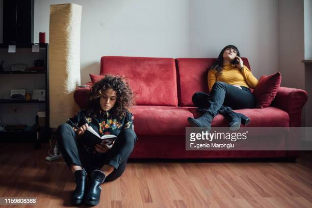 woman reading book, friend talking on smartphone on sofa - roommate stock pictures, royalty-free photos & images
