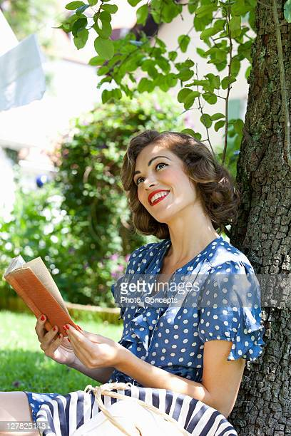 woman reading book in backyard - short hair stock pictures, royalty-free photos & images