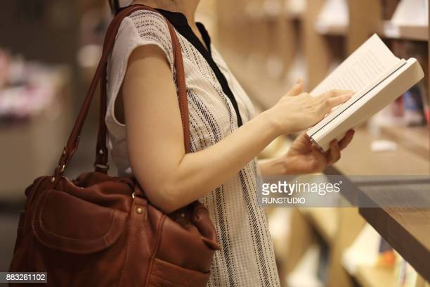 woman reading book in bookstore - shoulder bag stock pictures, royalty-free photos & images