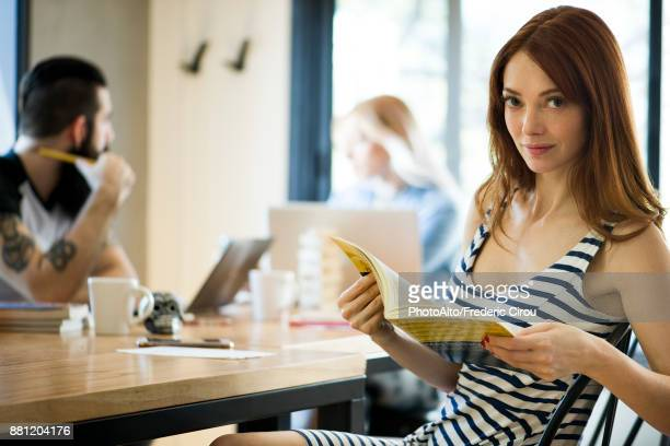 Woman reading book in cafe, portrait