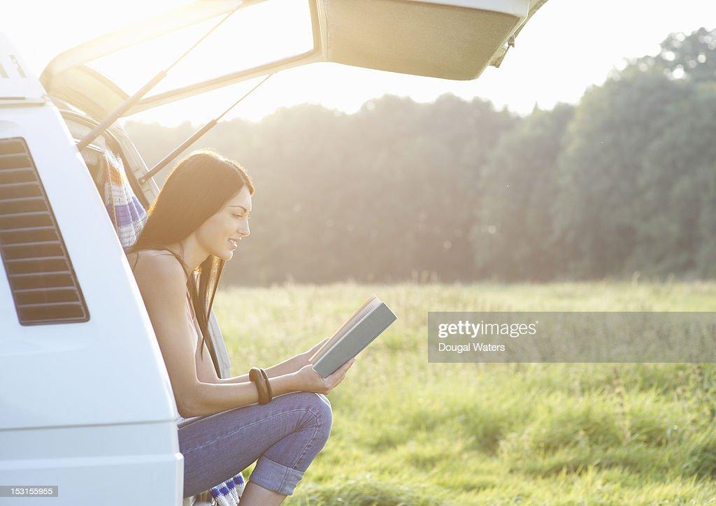 Woman reading book in camper van. : Stock Photo
