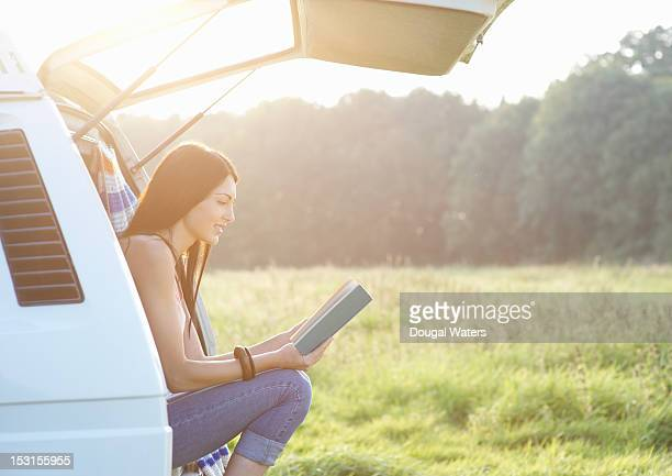 Woman reading book in camper van.