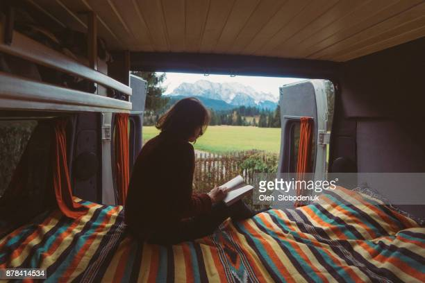 Woman reading book  in camper van with view on Alps