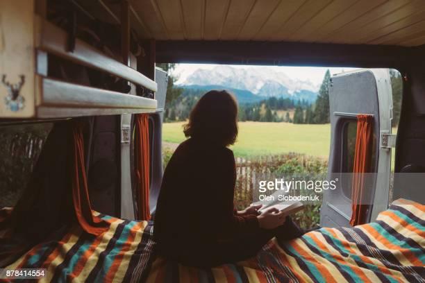 frau lesebuch im wohnmobil mit blick auf die alpen - wohngebäude innenansicht stock-fotos und bilder