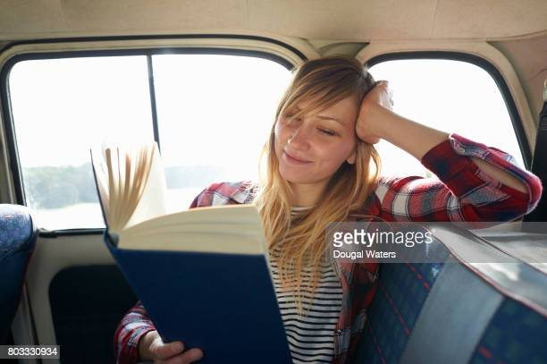 woman reading book in car. - eskapismus stock-fotos und bilder