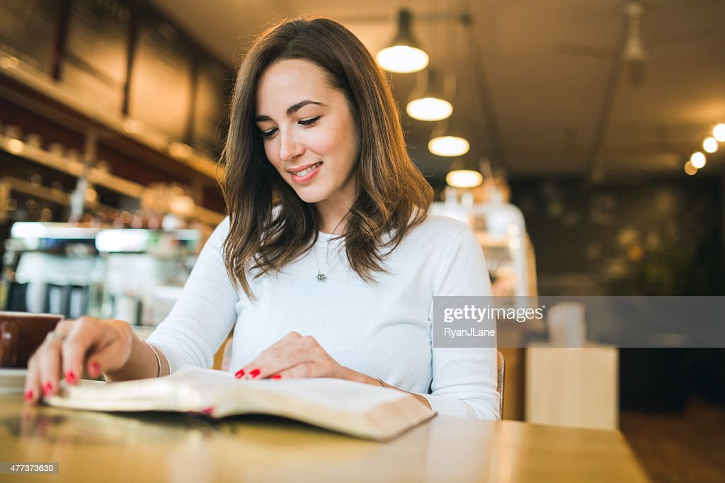 Woman Reading Book in Coffee Shop : Stock Photo