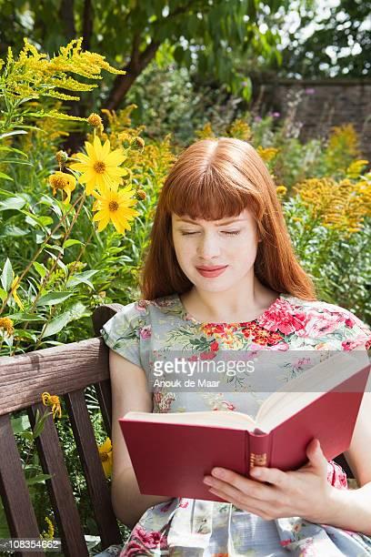 Woman reading book in flowergarden