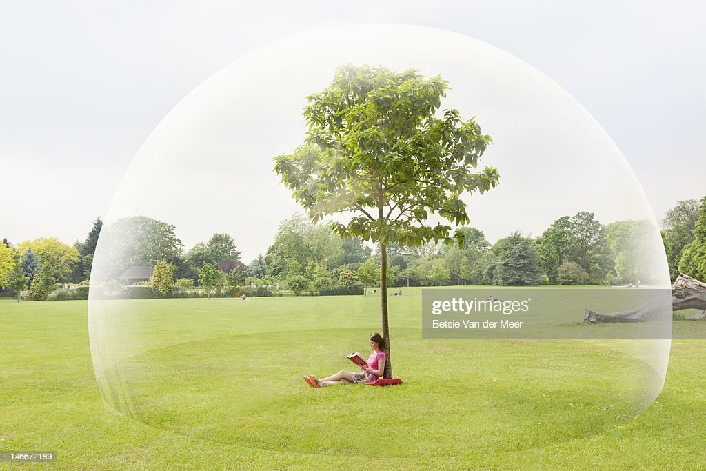 Woman reading book in park in large bubble : Stock Photo