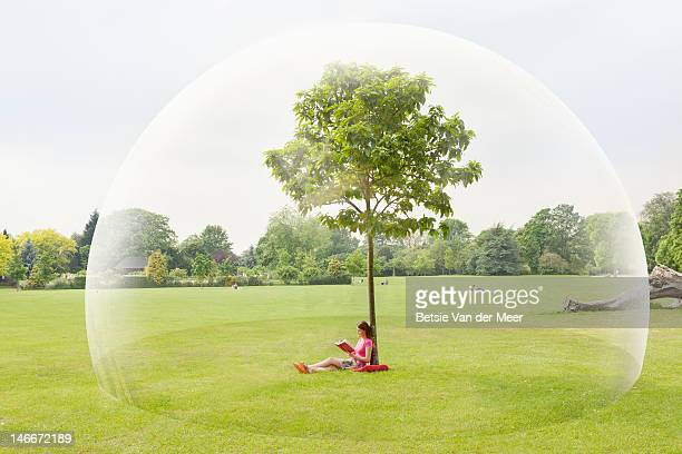 Woman reading book in park in large bubble