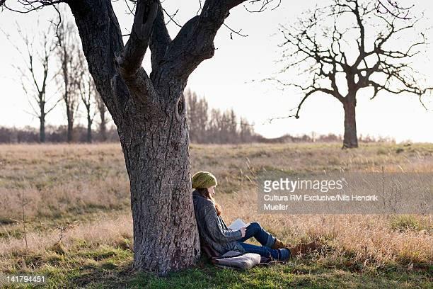Woman reading book in rural field