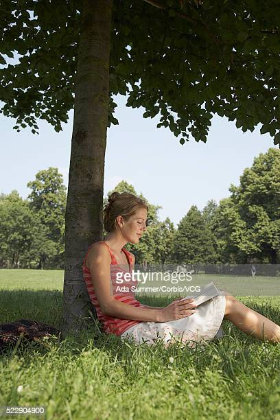 Woman reading book in shade under a tree