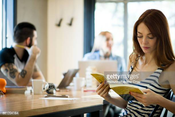 Woman reading book in shared office