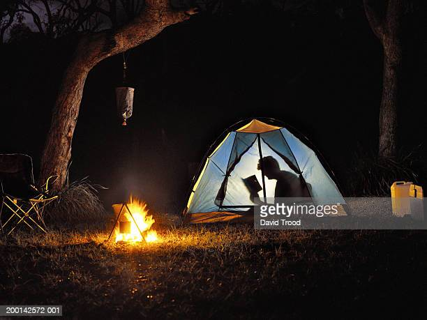 woman reading book in tent by camp fire, silhouette - 暖炉の火 ストックフォトと画像