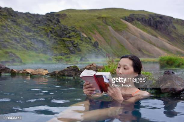 woman reading book in thermal pool at landmannalaugar - literature photos et images de collection