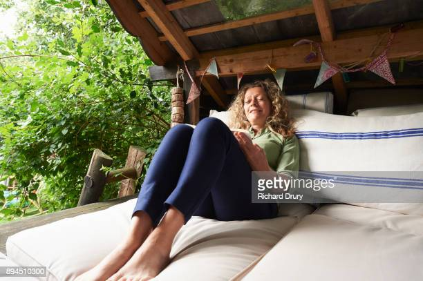 Woman reading book in treehouse