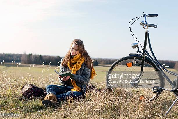 Woman reading book in wheatfield