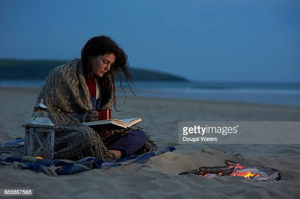 Woman reading book on beach at dusk.