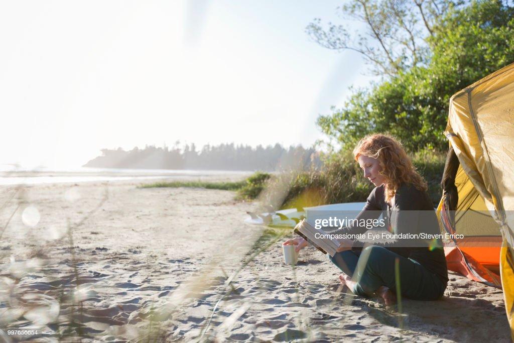Woman reading book on beach : Stock Photo