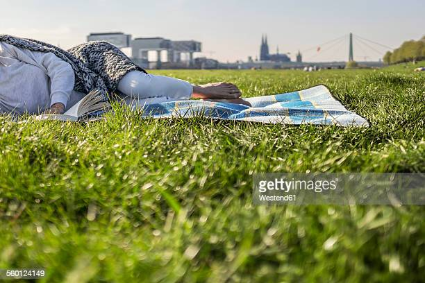 Woman reading book on blanket in meadow