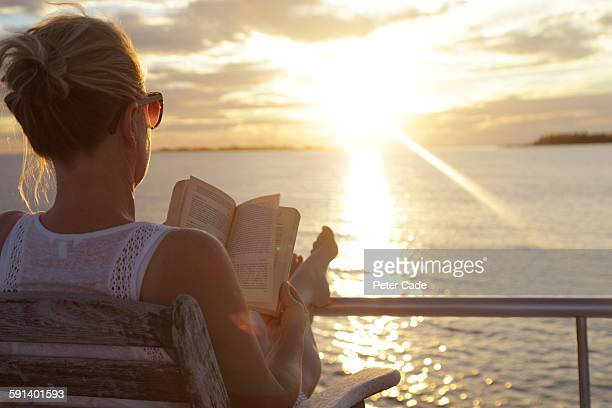 Woman reading book on deck of boat