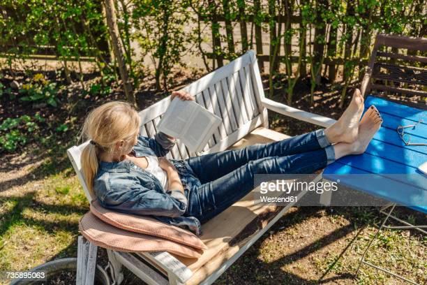 Woman reading book on garden bench