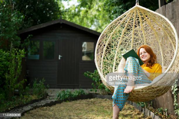 woman reading book on garden swing seat - reading stock pictures, royalty-free photos & images