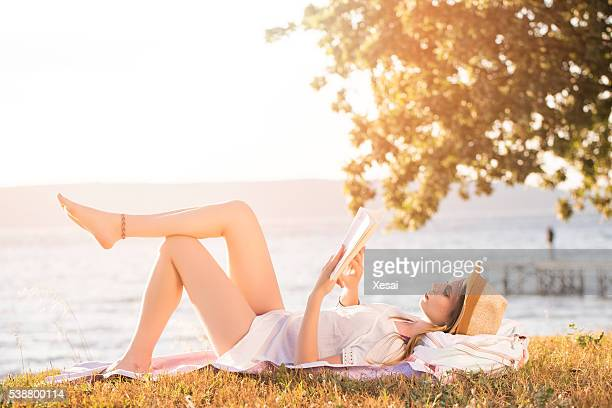 woman reading book on grass - one young woman only stock pictures, royalty-free photos & images