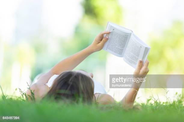 Libro de lectura de la mujer en el césped