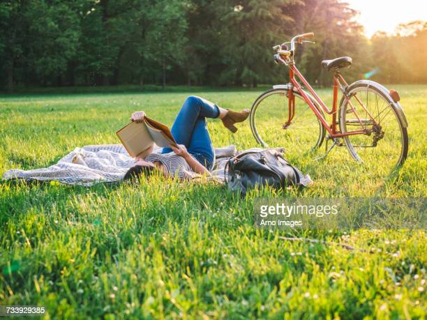 woman reading book on grass - lush stock pictures, royalty-free photos & images