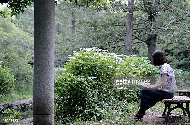 Woman reading book on park bench.