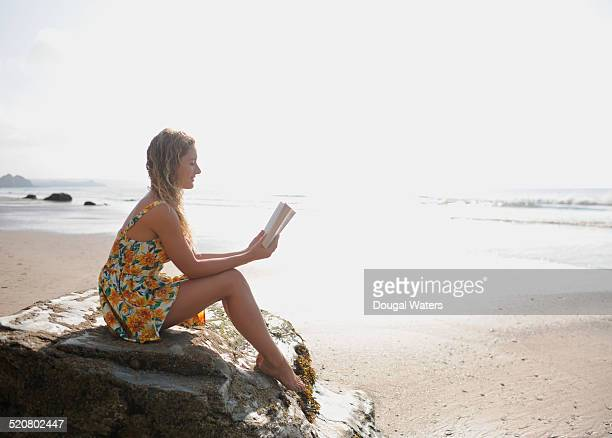 Woman reading book on rock at beach