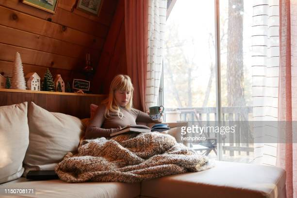 woman reading book on sofa at home - heshphoto stock pictures, royalty-free photos & images
