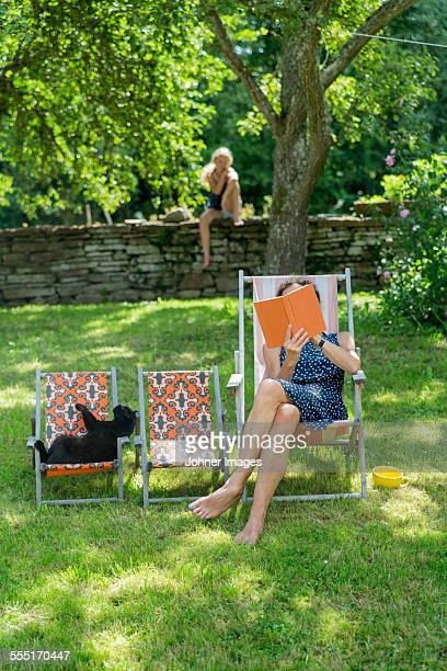Woman reading book on sun chair