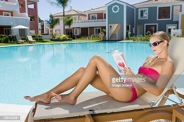 Woman reading book on sunlounger on vacation