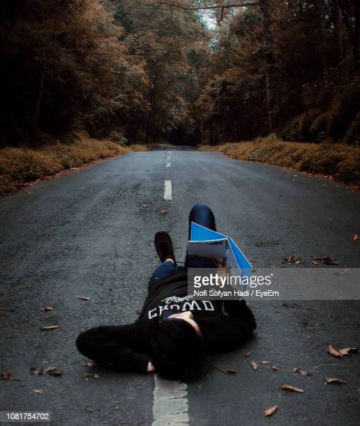 Woman Reading Book While Lying On Road Against Trees