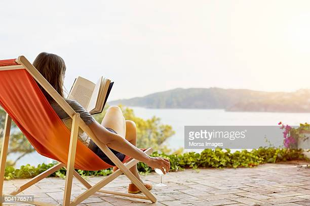 woman reading book while relaxing on deck chair - férias imagens e fotografias de stock