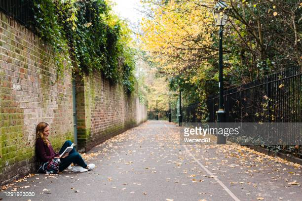 woman reading book while sitting by brick wall on footpath during autumn - sitting stock pictures, royalty-free photos & images