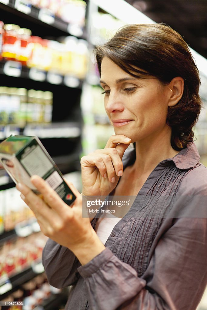 Woman reading box in grocery store : Stock Photo