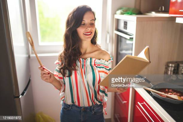 料理本を読んで料理をする女性 - 料理本 ストックフォトと画像