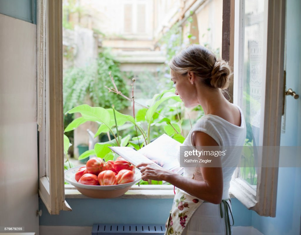 woman reading cookbook at open kitchen window : Stock Photo
