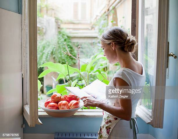 woman reading cookbook at open kitchen window - hair bun stock pictures, royalty-free photos & images