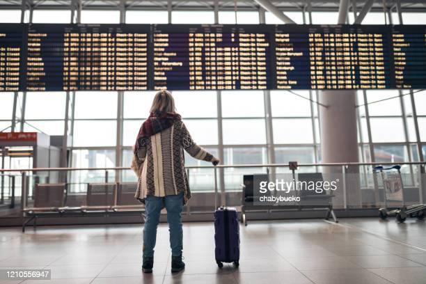 空港で出発ボードを読む女性 - 取り消し ストックフォトと画像