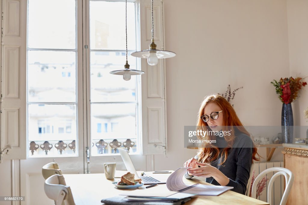Woman reading documents at table : Stock Photo