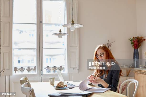 woman reading documents at table - hygge stock pictures, royalty-free photos & images
