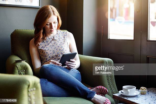 woman reading ebook on tablet in coffee shop - e reader stock pictures, royalty-free photos & images