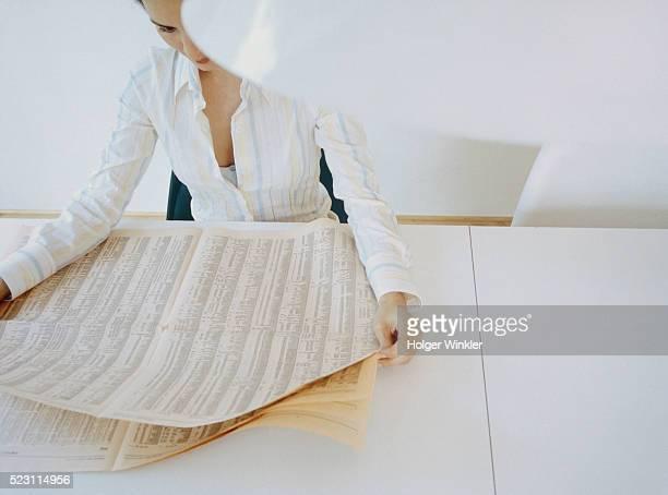 Woman reading financial newspaper