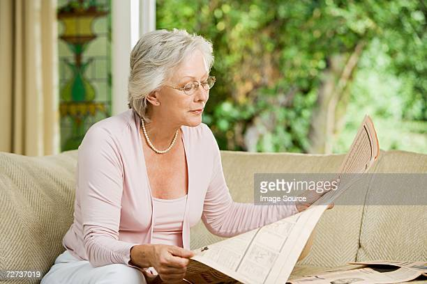 Woman reading financial newspaper