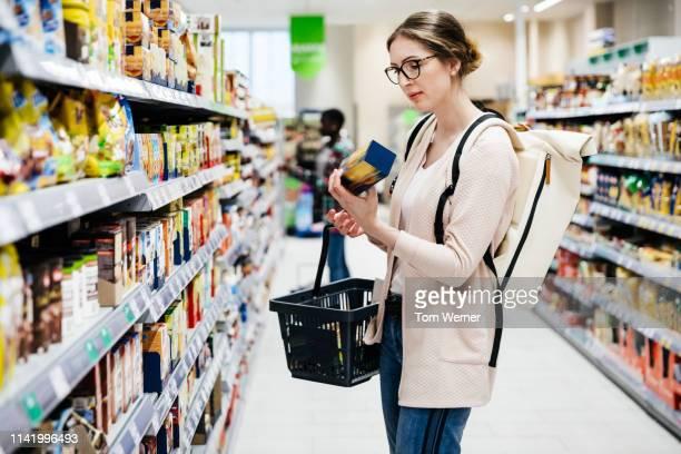 woman reading food item label in supermarket - einkaufen stock-fotos und bilder