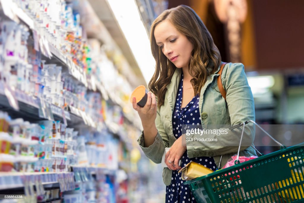 Woman reading food labels at grocery store : Stock Photo