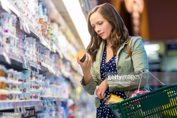 woman reading food labels at grocery store - consumentisme stockfoto's en -beelden